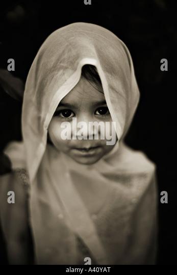 Three year old girl mixed race Pakistani English wears veil - Stock Image