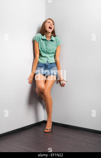 screaming woman stand in the corner of the room - Stock Image