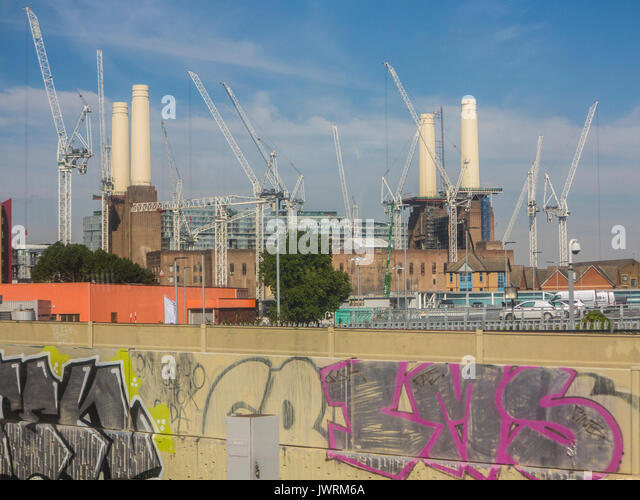 An unusual view of Battersea Power Station with a foreground of urban graffiti - Stock Image