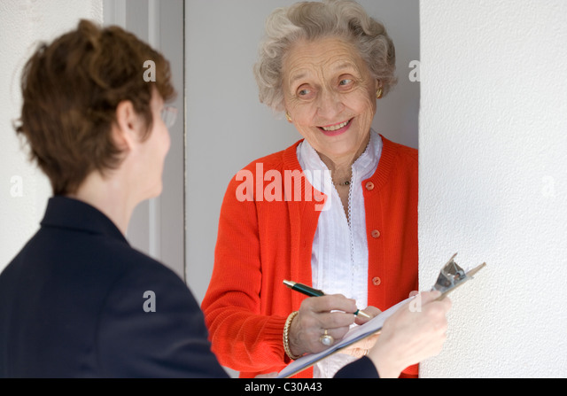 Attractive senior woman signing a document at her front door - Stock Image
