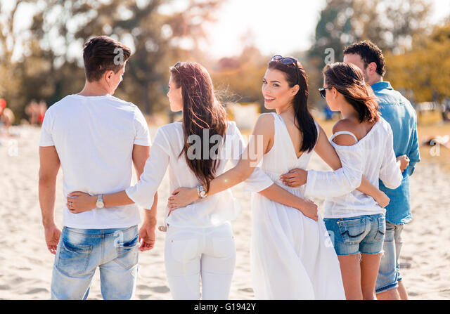 Group of young people holding hands on beach as a sign of friendship - Stock Image
