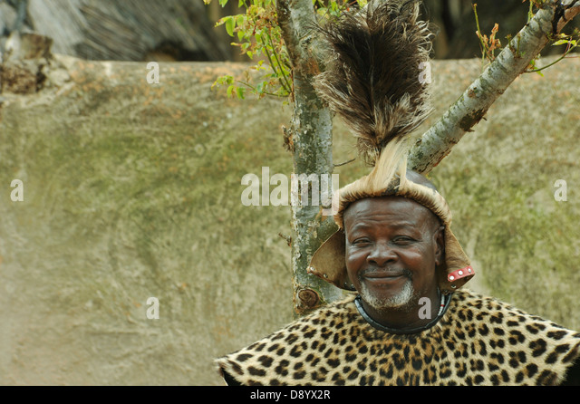 Head dress of Zulu chief Shakaland theme village KwaZulu-Natal South Africa smiling face of man ethnicity Travel - Stock-Bilder