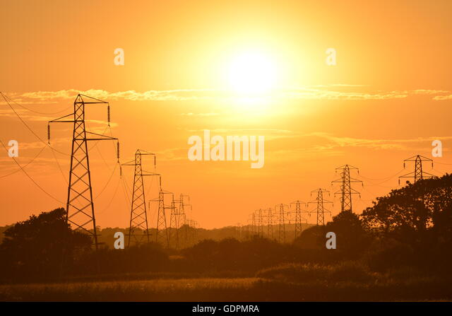 Sun setting behind electricity power lines - Stock Image