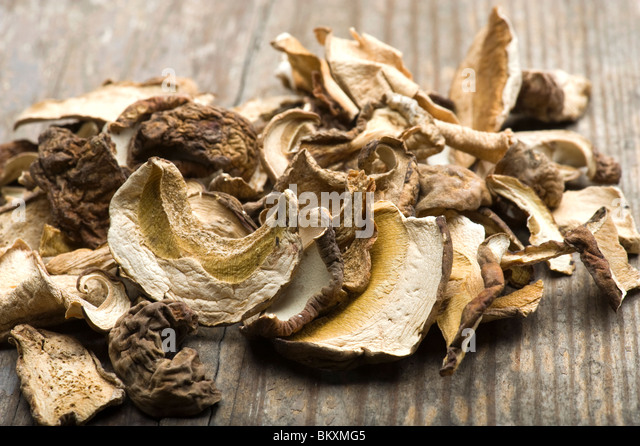 Close-up Of Dried Porcini Mushrooms On Wooden Table - Stock Image