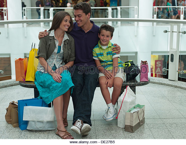 Smiling family in shopping mall relaxing on bench - Stock-Bilder