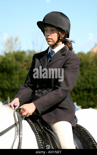 A teenage girl in show jumping outfit sits smartly on her horse - Stock Image