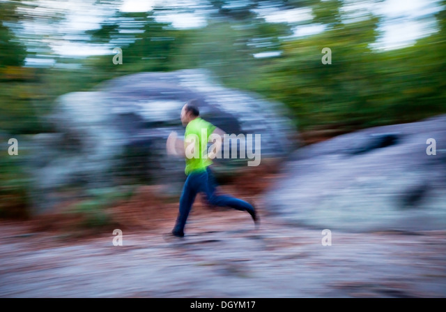 blurred motion, man running outdoors - Stock Image