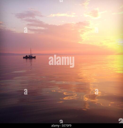 Small boat at sea in colorful sunset - Stock Image