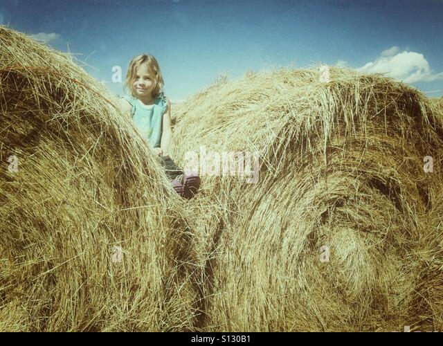 A girl sits wedged between two round hay bales. - Stock Image