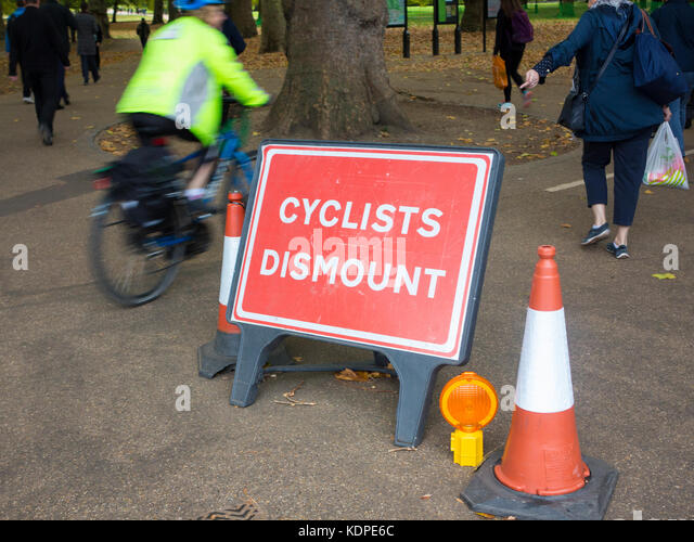 A woman points to a sign instructing cyclists to dismount as the cyclist ignores her and the sign - Stock Image