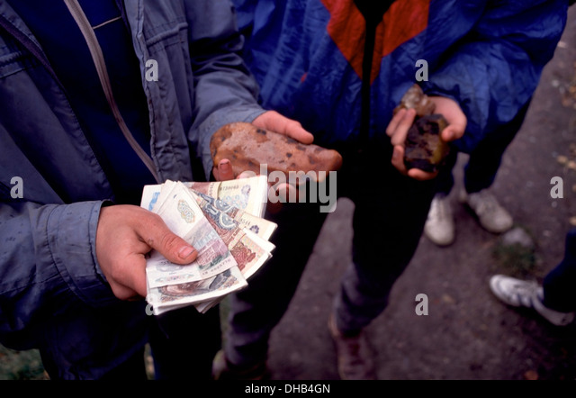 Teenage boy holding amber and the Russian Rubles he has made in one morning selling other amber pieces in Yantarny, - Stock Image