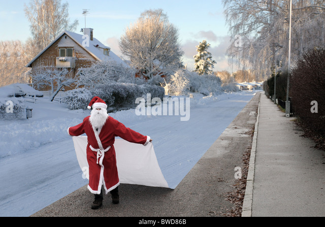 Santa Claus changing the season to winter by laying a sheet of snow on the ground. - Stock Image