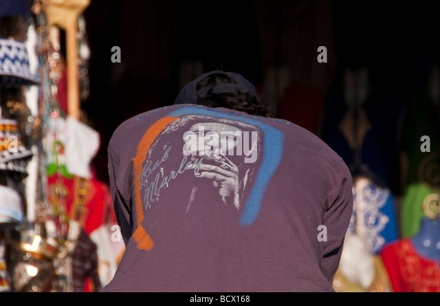 Egypt Kom Ombo souvenir seller wears Bob Marley shirt smoking marijuana - Stock Image