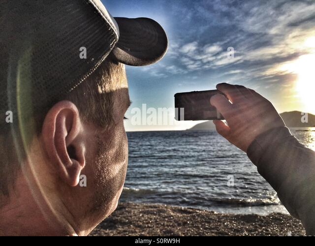 Man taking a photo with an iPhone - Stock Image