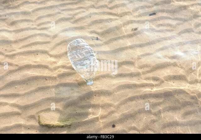 Plastic bottle in shallow sea water, environmental pollution concept. - Stock Image