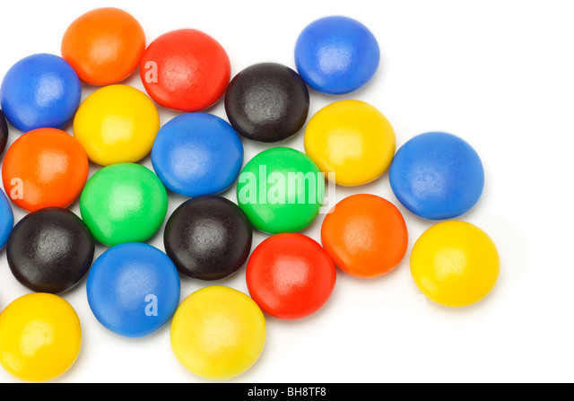 Colorful chocolate button candies spreaded randomly on white background - Stock Image