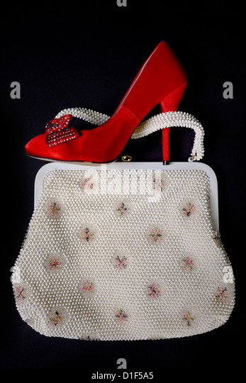 a red shoe with high heels on a vintage handbag - Stock Image