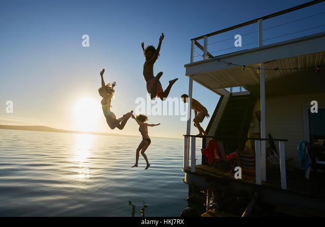 Young adult friends jumping off summer houseboat into sunset ocean - Stock-Bilder