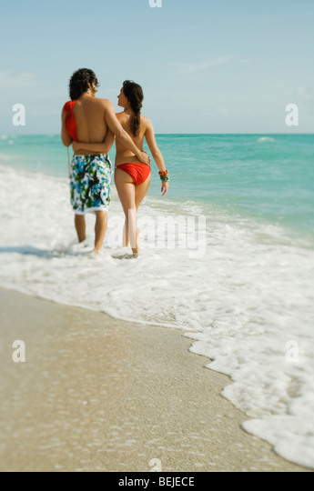 Rear view of a young couple walking on the beach - Stock-Bilder