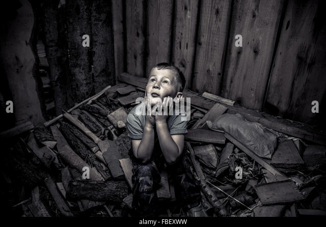 High Angle View Of Trapped Boy Sitting On Rubble In Room - Stock-Bilder