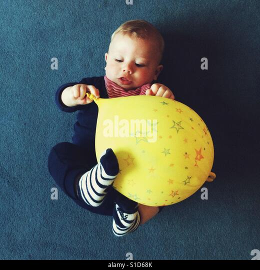 Baby boy playing with a yellow balloon - Stock-Bilder