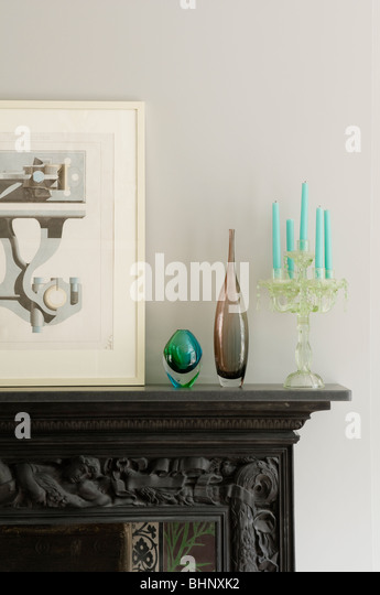Artwork, glassware and candelabra on carved mantelpiece - Stock Image