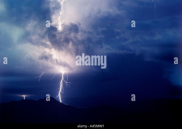 Lightning  strikes against a stormy dark blue sky over the silhouette of mountains in Southern Arizona USA. - Stock Image