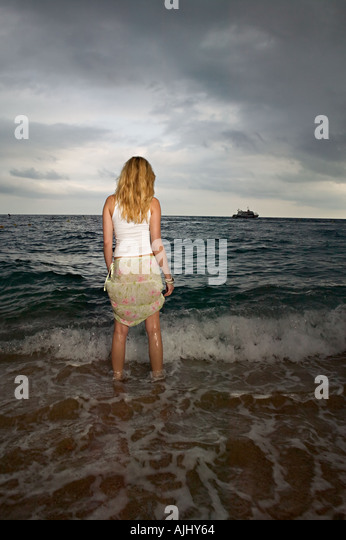Woman standing in the sea - Stock Image