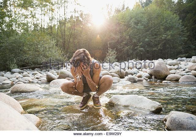 Teenage boy splashing water on face in creek - Stock Image