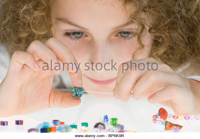A young girl threading beads onto a thread - Stock Image