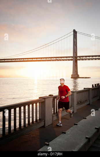 Man running on city street - Stock Image