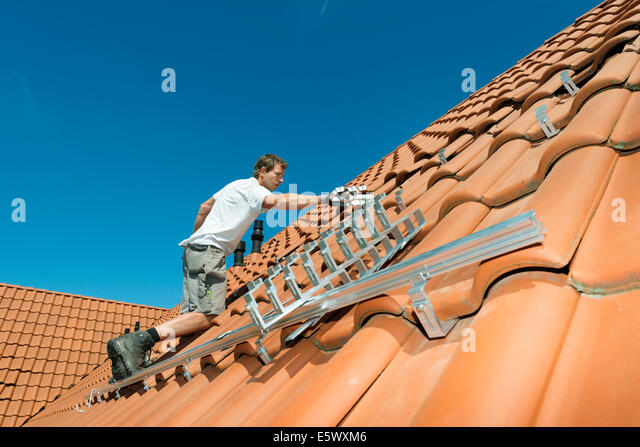 Worker installing framework for solar roof panels on new home, Netherlands - Stock Image