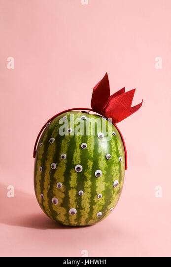 Freak watermelon wearing a crown on a pink background - Stock Image