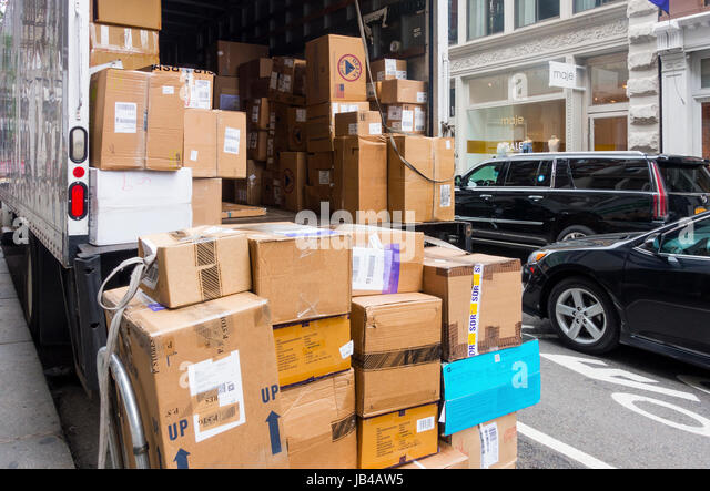 FedEx truck delivering boxes on a busy crowded street in New York City - Stock Image