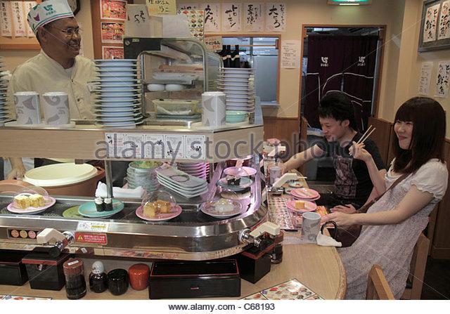Tokyo Japan Ikebukuro kanji hiragana katakana characters sushi bar restaurant conveyor belt Asian man woman couple - Stock Image