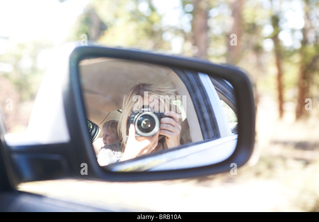 Woman taking pictures in side mirror of car - Stock Image
