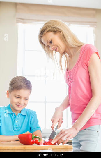 Boy looking at mother slicing red bell pepper in kitchen - Stock Image
