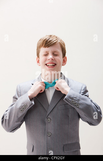 Boy wearing grey suit adjusting bow tie, studio shot - Stock Image