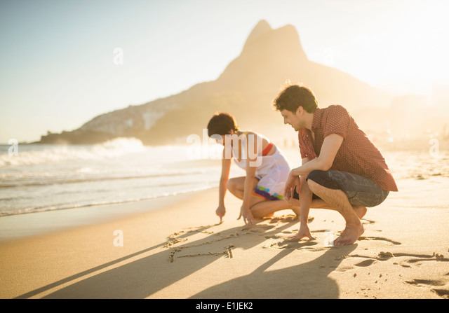 Young couple writing on sand, Ipanema Beach, Rio, Brazil - Stock Image