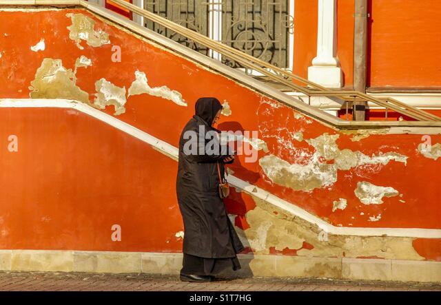Old woman orange background - Stock Image