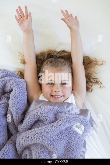 Little girl covered with soft blanket - Stock Image