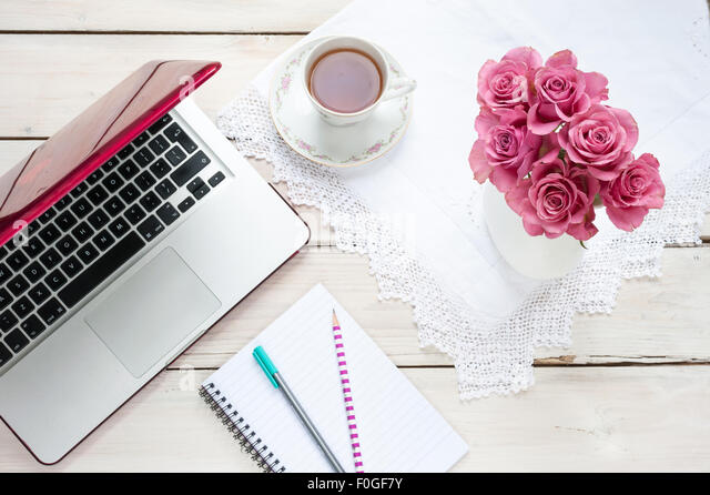 working from home - laptop, pink roses, teacup, notebook and pens on a desk - Stock-Bilder