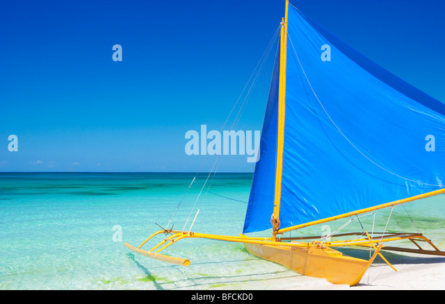 Yellow boat with blue sail in shallows Boracay; The Visayas; Philippines - Stock Image