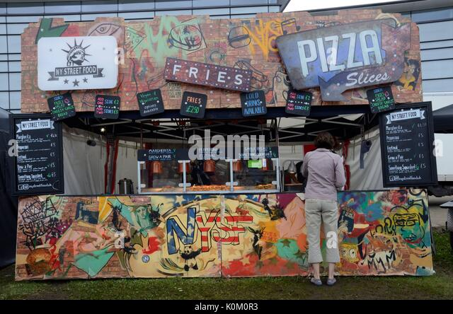 colourful street food van stand selling pizza and fries chips at a food festival Swansea Food Festival - Stock Image