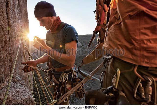 Rock climber inspecting rope, Unaweep Canyon, Colorado, America, USA - Stock Image