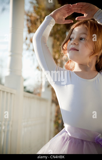 Girl dancing in ballet costume on porch - Stock Image
