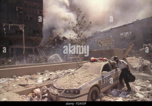 Policeman reaching into a debris covered police car after 9-11 terrorist attack in NYC. At left is still standing - Stock-Bilder