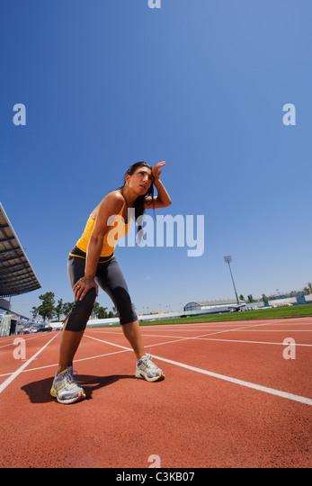 Female athlete standing at stadium - Stock Image