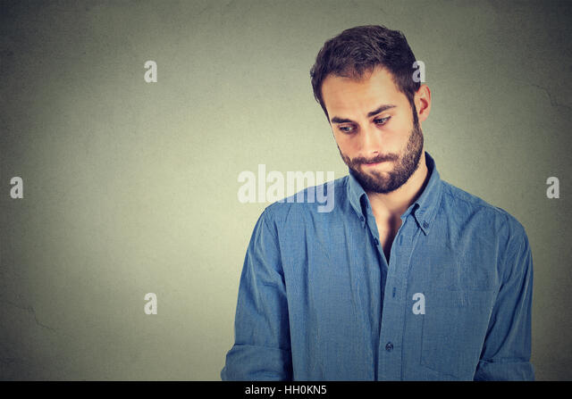 Lack of confidence. Shy young handsome man feels awkward isolated gray wall background. Human emotion body language - Stock Image
