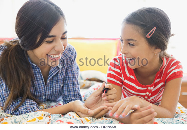 Sisters painting fingernails on bed - Stock Image
